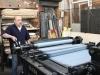 Patrick, de l'atelier Idem, manie la presse pour le premier passage de couleurs sur les lithographies